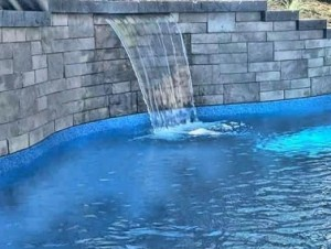 Water sheer feature in pool retaining wall